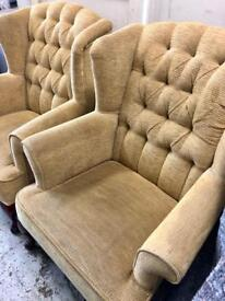 A pair of mustard cloth wing chairs