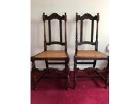 Set of four carved oak dining chairs in good condition with cane seats.