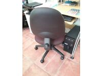 Computer chair, tilt and height adjustable, upholstered dark maroon.