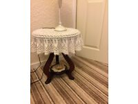 2 ornate circular wooden tables with shelf.