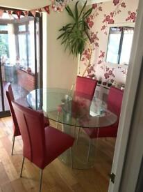 Glass dining table and four red leather chairs