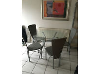 Round glass dining table with chrome legs and 4 grey leather effect chairs.