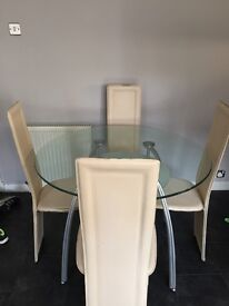 Glass dining table with four cream leather chairs