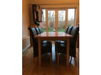 Debenhams extending oak dining table and six brown leather high back chairs