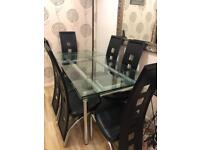 Large extendable glass dining table with 6 black chairs