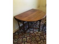 Solid dark oak gate leg drop leaf table and 6 matching Windsor wheel back chairs
