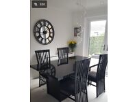 Black extendable dining table with 6 chairs