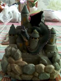Indoor water fountain. Design is of a castle with a moat and a dragon wrapped around the turrets.