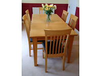 Extending oak dining table and six chairs