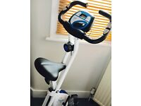 Davina exercise bike. Displays calories, pulse, speed, distance, time. Folds up for easy storage.