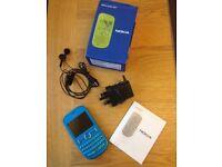 Nokia Asha 201 Aqua - Mobile phone, charger and headphones