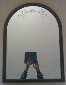 Arch engraved mirror in dark mahogany frame.