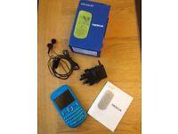 Nokia Asha 201 Aqua- Mobile phone, charger and headphones