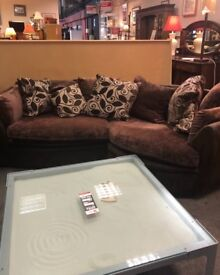 Brown couch and separate swivel chair with cushions.