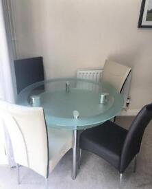 Round four seater glass dining table with four leather dining chairs