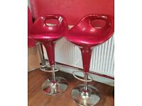 2 red gas lift bar stools