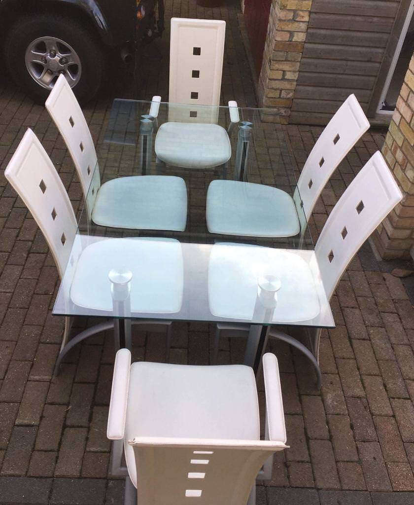 Large glass dining table and 6 cream leather chairs