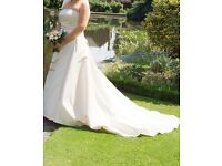 A beautiful strapless champagne colour satin wedding dress with train