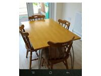 Wooden dining table with 4 chairs and cushions