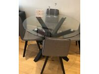 Glass topped dining table and four grey fabric dining chairs