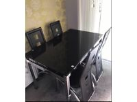 Black dining table for sale. Good condition. Comes with four slick chairs.