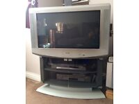 Old style Sony 30'' colour flat screen TV, silver framed, complete with glass fronted two tier stand