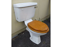 Close coupled toilet suite, complete with wooden seat aand cover.