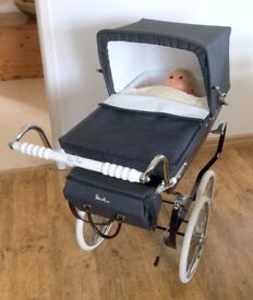 For sale – Silver Cross, navy blue dolls pram, with changing bag, doll, clothes and bedding.