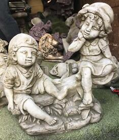 Big stone statue boy and girl on seesaw garden