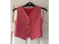 Red and white striped waistcoat and black cap.