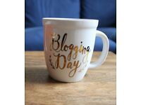 "White Mug with Gold lettering, saying ""Blogging Day"""