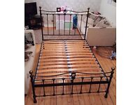 Black wrought iron double bed frame with brass detail and mattress