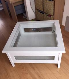 White glass topped table with glass sides with two opening out.