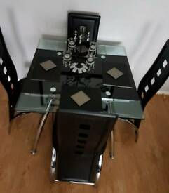 Extending black glass dining table with 4 chairs