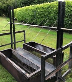 Heavy duty, hog roast barbeque with two free-standing side log baskets.