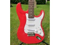 a 'Stratocaster' style guitar in red, excellent playing condition.