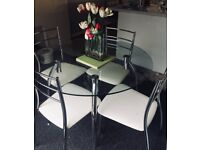 Glass Round Dinning Table with Four Chairs. Faux leather