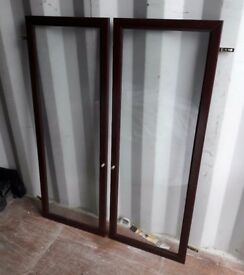 Pair of dark wood glass cabinet doors with hinges 116 x 43cm
