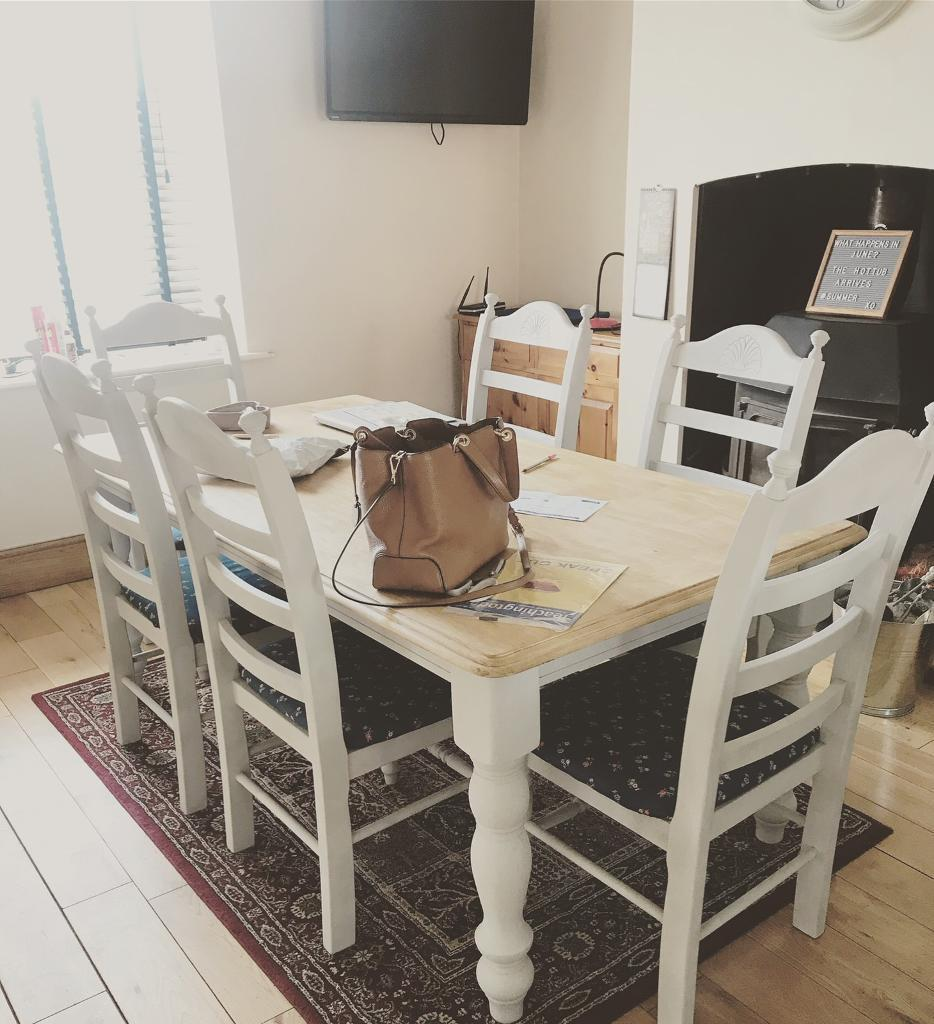 large farmhouse table painted in light grey with six solid chairs to
