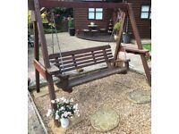 garden wooden swing supported bench seats three.
