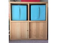 IKEA wooden cube storage unit with blue fabric draws and cupboards