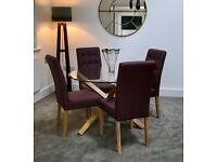 Unused (on display in show home) round glass table, oak legs, and plum upholstered dining chairs