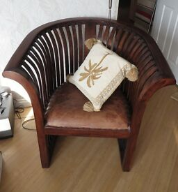Feature arm chair, dark solid wood construction with leather seat. Light use only.
