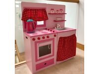 Two toy kitchen units with lots of accessories