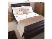 Sleigh brown faux leather double bed.