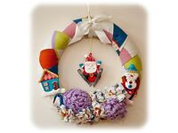 Fabric Christmas wreath with Santa, snowman and bunches of festive flowers.