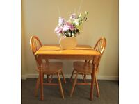 Dining table and 2 matching chairs solid wood pine carved table and wheel back chairs
