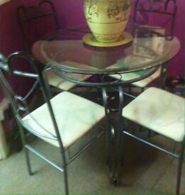 Round glass silver ironwork table and 4 chairs