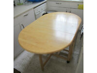 BEECH DROP LEAF TABLE IN VERY GOOD CONDITION. FOLDS SMALL, ON CASTERS. COLLECT PRIMROSE HILL NW1