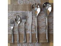 Cutlery looks like silver or steel. Knives, forks, spoons, desert forks, salad servers